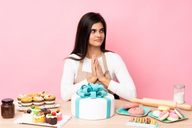 Шеф-кондитер с большим тортом в столе над розовой стеной что-то замышляя