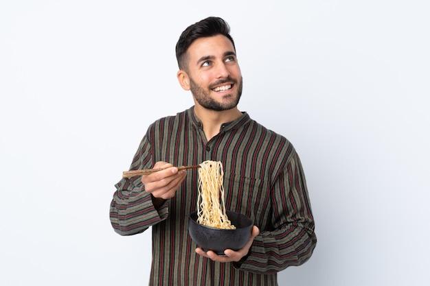 箸で麺のボウルを押しながら見上げる孤立した壁の上の若い男