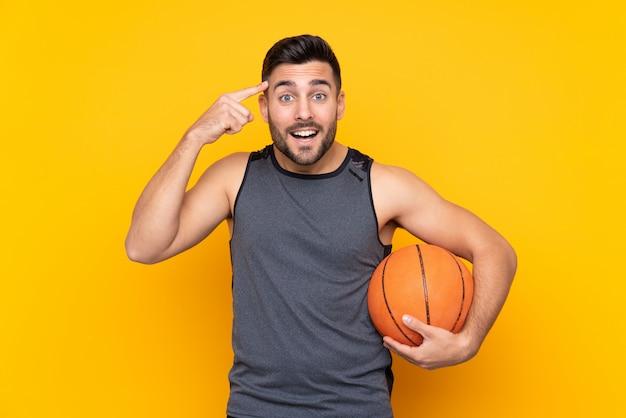 Красивый молодой человек баскетболиста над изолированной белой стеной намереваясь реализовать решение