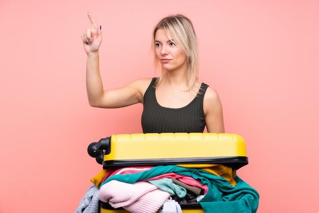 透明な画面に触れる分離のピンクの壁の上の服でいっぱいのスーツケースを持つ旅行者女性