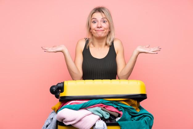 混乱した表情で疑問を持つ分離ピンクの壁の上の服の完全なスーツケースを持つ旅行者女性