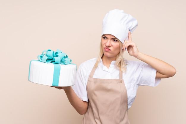 孤立した壁の上の大きなケーキを持つ若いロシア人女性