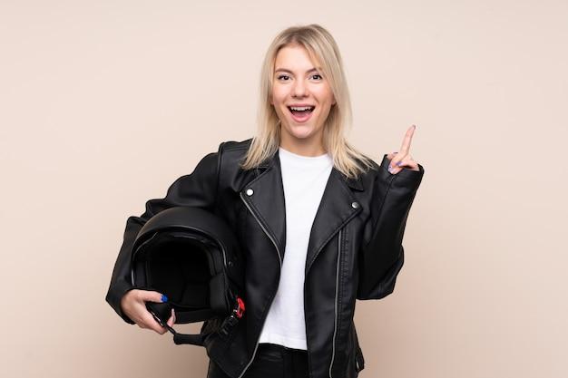 素晴らしいアイデアを指している孤立した壁の上のオートバイのヘルメットを持つ若いブロンドの女性