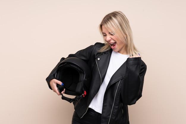Молодая блондинка с мотоциклетным шлемом над изолированной стеной празднует победу
