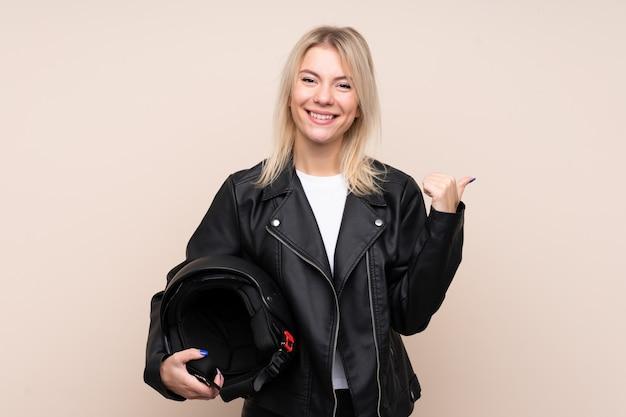 Молодая блондинка с мотоциклетным шлемом над изолированной стеной, указывающей на сторону, чтобы представить продукт