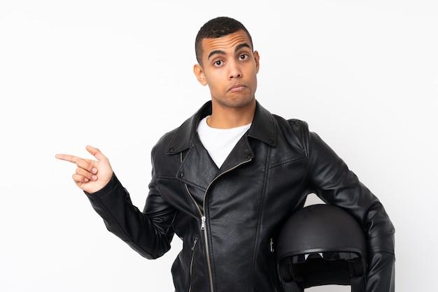 疑いのある側面を指している分離の白い壁の上のオートバイのヘルメットを持つ若いハンサムな男
