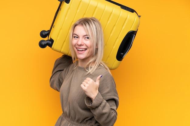 Молодая белокурая женщина над изолированной желтой стеной в каникулах с чемоданом перемещения и с большим пальцем руки вверх