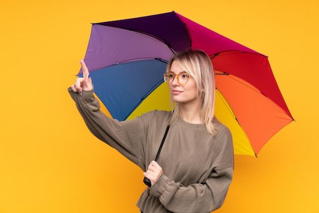 透明なスクリーンに触れる分離の黄色の壁に傘を置く若いブロンドの女性