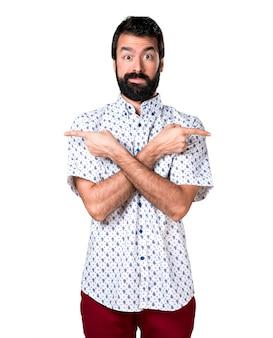 Красивый брюнетка с бородой, указывающий на боковые стороны, которые сомневаются