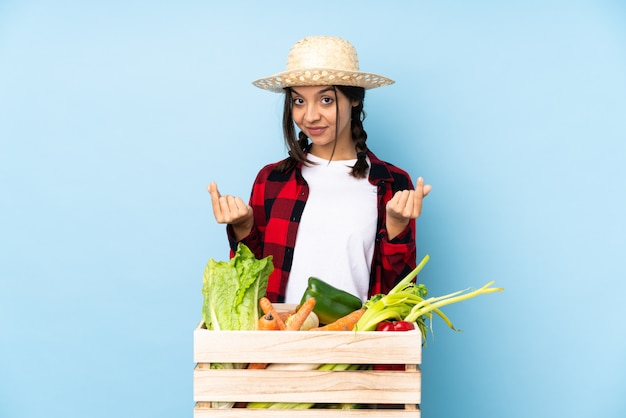 お金のジェスチャーを作る木製のバスケットで新鮮な野菜を保持している若い農家の女性