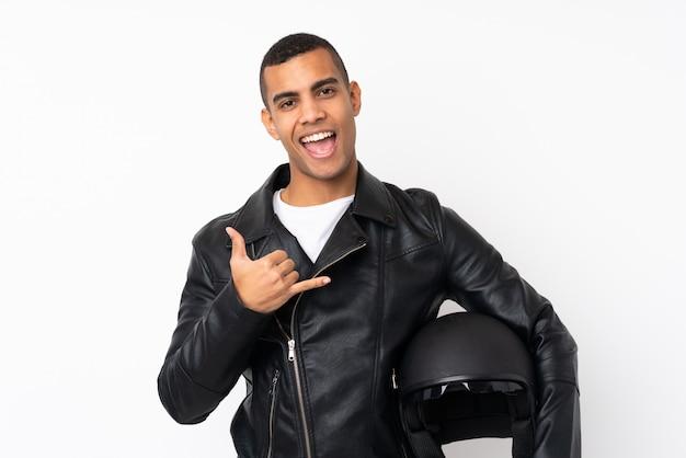 Молодой красавец с мотоциклетным шлемом на белом фоне, делая жест телефона