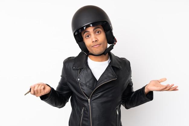 孤立した白い壁の上のオートバイのヘルメットを持つ若いハンサムな男