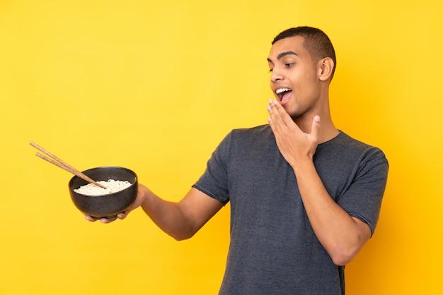 箸で麺のボウルを押しながら驚きとショックを受けた表情で孤立した黄色の壁の上の若いアフリカ系アメリカ人の男