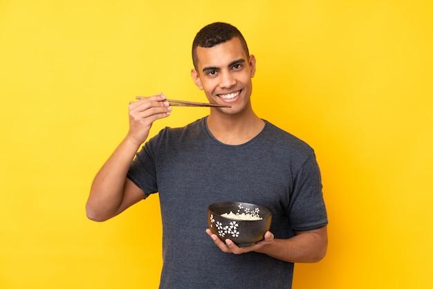 Молодой афроамериканец человек над желтой стене, держа миску лапши с палочками