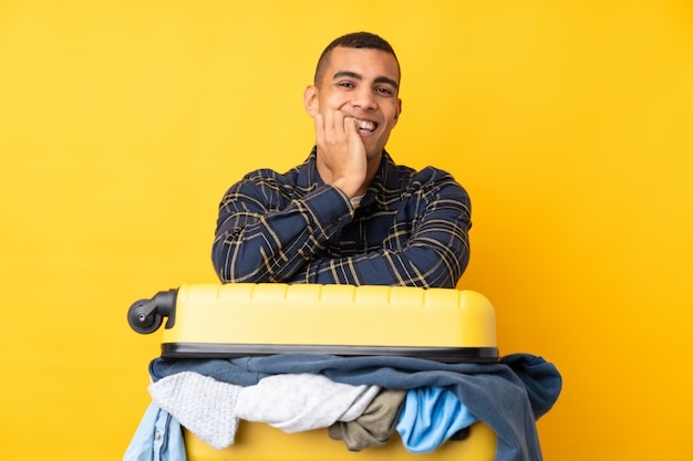 Путешественник человек с чемоданом, полным одежды на изолированной желтой стене нервной и испуганный