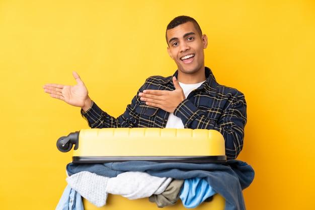 来て招待する側に手を伸ばす孤立した黄色の壁の上の服でいっぱいのスーツケースを持つ旅行者男
