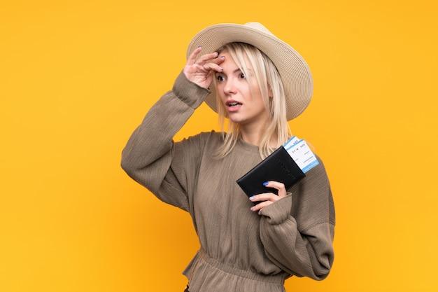 遠くに何かを見ながらパスポートと飛行機のチケットと休暇で孤立した黄色の壁の上の若いブロンドの女性
