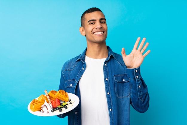 幸せな表情で手で敬礼分離の青い壁にワッフルを置く若いハンサムな男