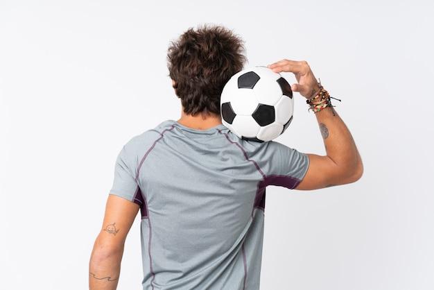 サッカーボールで孤立した白い壁の上の若い白人男