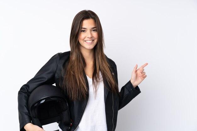 Молодая женщина с мотоциклетным шлемом на белом фоне, указывая пальцем в сторону
