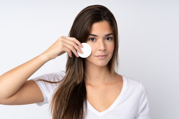 Девочка-подросток над изолированной стеной с ватным тампоном для снятия макияжа с ее лица