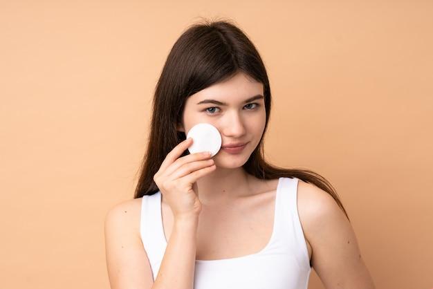 Молодая девушка-подросток над стеной с ватным тампоном для снятия макияжа с лица