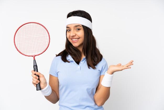 Молодая женщина игрока бадминтона над белой стеной представляя идею пока смотрящ усмехающся к