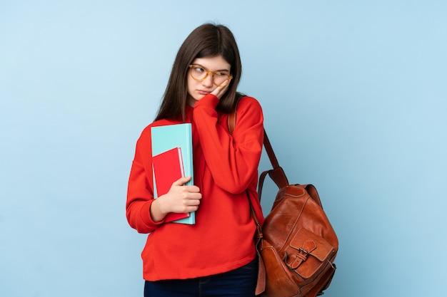 Молодая девушка студента подростка держа салат над голубой стеной несчастной и разочарованной