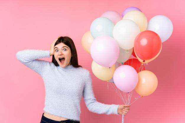 Молодая девушка подросток держит много воздушных шаров над розовой стеной с удивленным выражением лица