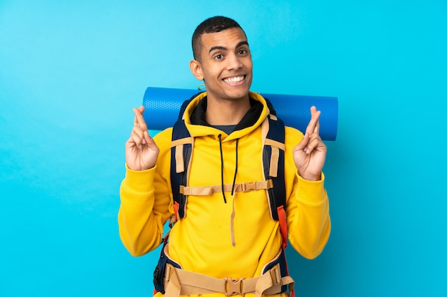 指を交差で分離の青い壁の上の大きなバックパックを持つ若い登山家男