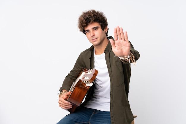彼女の手で停止ジェスチャーを作る分離の白い壁の上のギターを持つ若い白人男