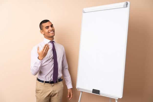 ホワイトボードでプレゼンテーションを行い、手に来るように招待して孤立した壁の上の若いビジネスマン