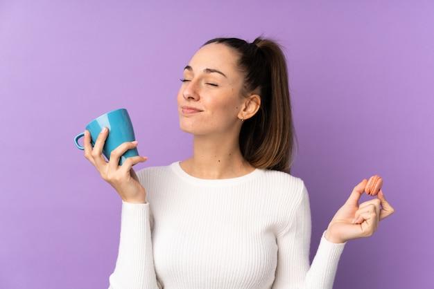 カラフルなフランスのマカロンとミルクのカップを保持している孤立した紫色の壁の上の若いブルネットの女性