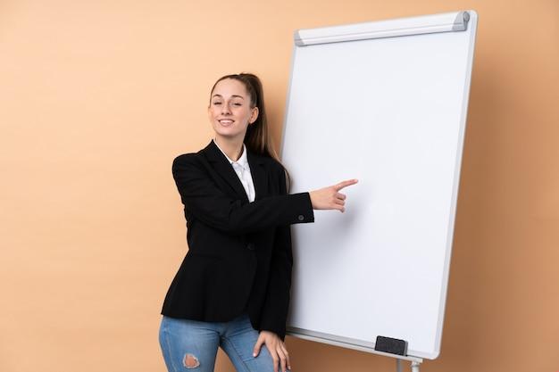 ホワイトボードにプレゼンテーションをし、それを書く孤立した壁の上の若いビジネス女性