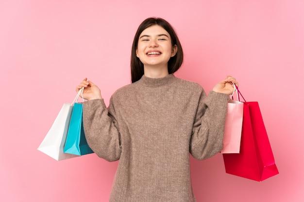 Молодая девушка подросток над розовой стеной, холдинг сумок и улыбается