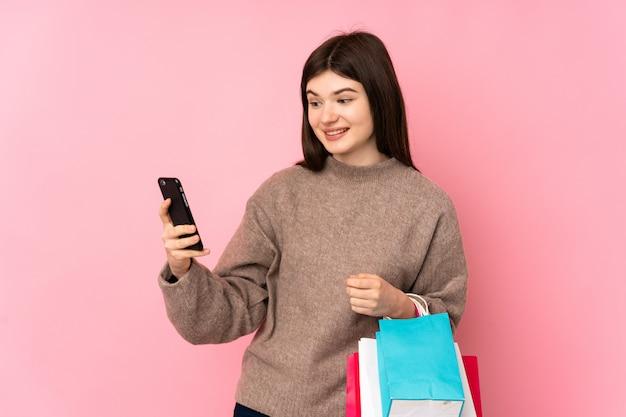 Молодая девушка подростка над розовой стеной держа хозяйственные сумки и писать сообщение с ее сотовым телефоном к другу