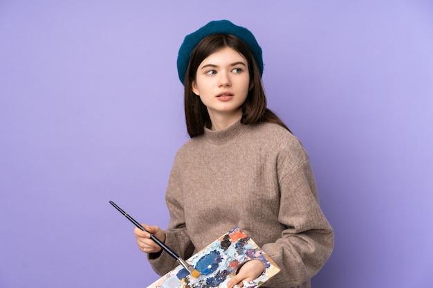 Молодая девушка художника держит палитру над фиолетовой стеной