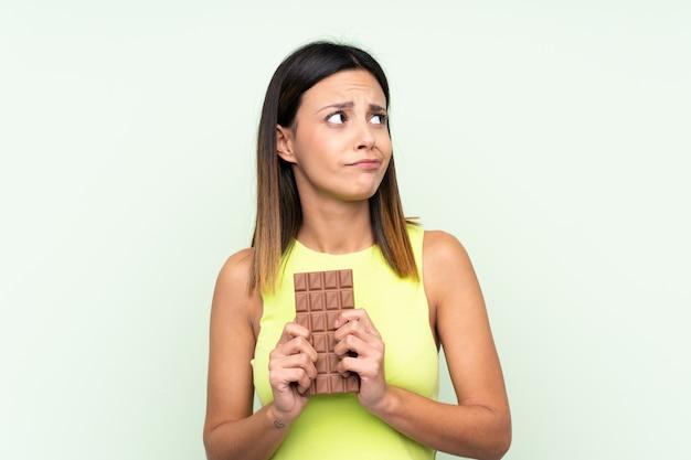 Женщина над зеленой стеной принимая таблетку шоколада и имея сомнения