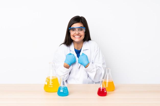 Молодая научная женщина в таблице с удивленным выражением лица