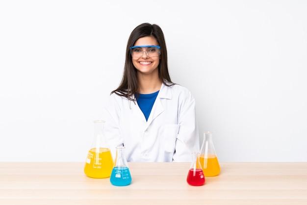 腕を組んで、楽しみにしてテーブルで若い科学的な女性