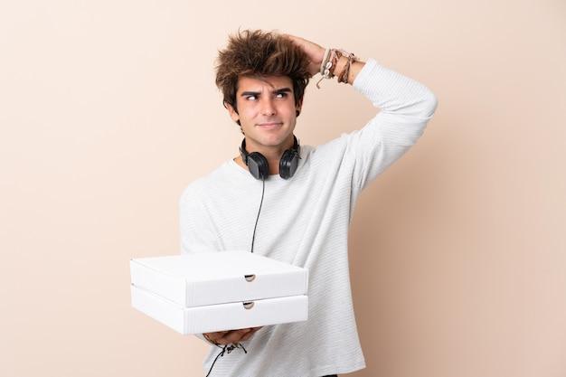 疑いがあると混乱の表情を持つ孤立した壁にピザを置く若いハンサムな男