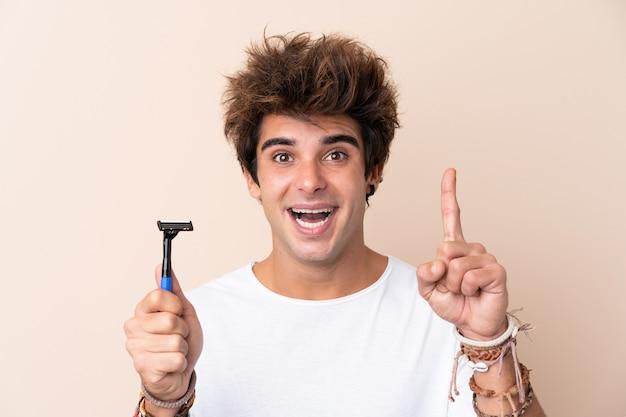 Молодой красавец брить бороду, указывая на отличную идею