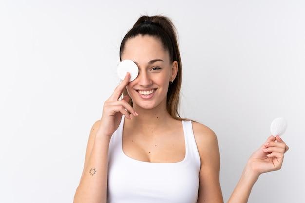 Молодая брюнетка женщина над белой стеной с ватным тампоном для снятия макияжа с ее лица и улыбается