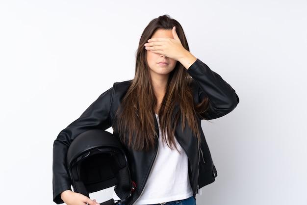 手で目を覆っている孤立した白い壁の上のオートバイのヘルメットを持つ若い女性