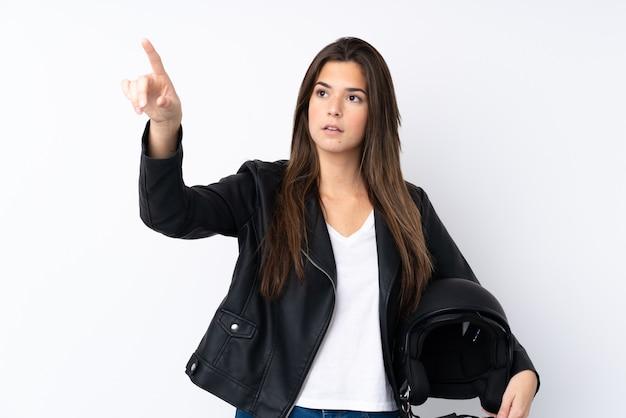 透明なスクリーンに触れる分離の白い壁にオートバイのヘルメットを持つ若い女性