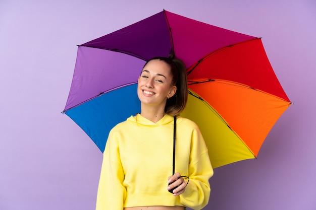 Молодая брюнетка женщина, держащая зонтик над изолированные фиолетовые стены с счастливым выражением