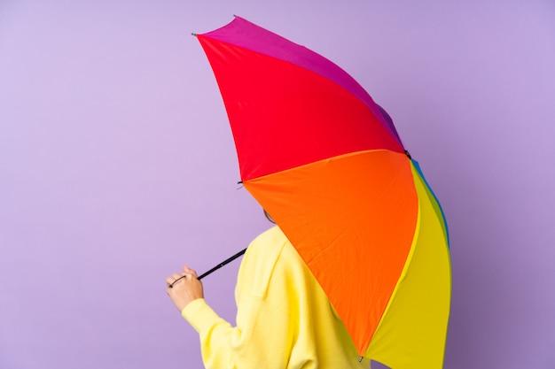 Молодая брюнетка женщина, держащая зонтик над фиолетовым стены в заднем положении