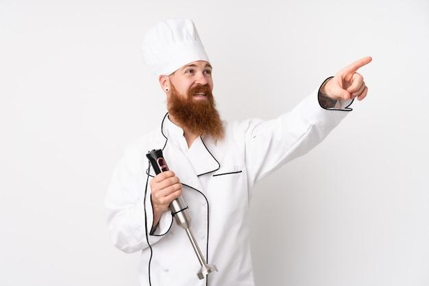 透明なスクリーンに触れる分離の白い壁にハンドミキサーを使用して赤毛の男