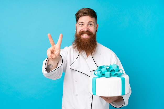 笑顔と勝利のサインを示す分離の青い壁に大きなケーキをかざす長いひげと赤毛のパティシエ