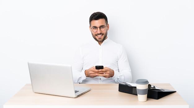 携帯電話でメッセージを送信する職場の青年実業家